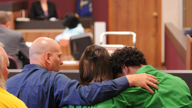 The Skinner family keep their heads down as they listen to testimony during the 2011 trial of Jonathan Kurtz.