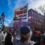 Demonstrators parade down State Street during a march and protest organized by Rising Tide Vermont against a proposed natural gas pipeline in Montpelier on Saturday, October 24, 2015.  The pipeline opponents say the pipeline would bring gas to Vermont that was extracted elsewhere using fracking.