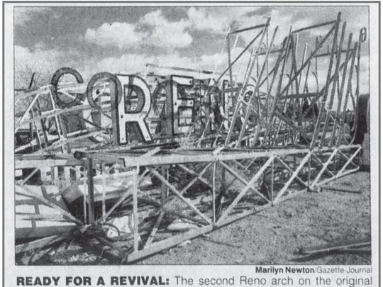 """Original caption: """"Ready for a revival: The second Reno arch on the original framework is resting in the sign graveyard behind Young Electric Sign Co. on East Glendale Avenue."""""""