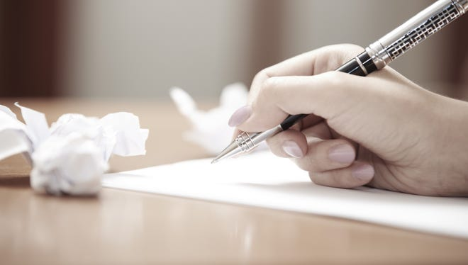 Human hand with pen writing document and crumpled paper on table