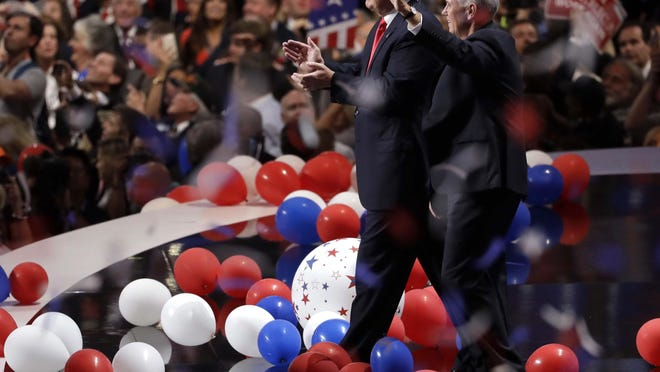 Then Republican presidential candidate Donald Trump, center left, walks with vice presidential candidate Mike Pence after Trump's acceptance speech on the final day of the 2016 Republican National Convention.