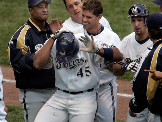 Milwaukee Brewers' Carlos Lee gets a helmet pounding from Jeff Cirillo and teammates after his bloop hit drove in the winning run in the 9th inning at Miller Park Thursday, May 5, 2005.