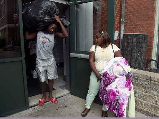 Smitty St. Louis, 16, helps his mother Marianie Sanon carry laundry outside of their apartment in Evansville recently.   Sanon was one of 21 Haitian passengers injured when the van they were being transported in wrecked on Interstate 69 while traveling to their worksite on Sept., 24, 2015. Two passengers died and several others, including Sanon, were severely injured.