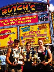 Aly Lupinetti, center, husband Matt Meyer, left, and mother Lynne Lupinetti celebrate wins by Butch's Smack Your Lips BBQ of Mount Laurel, N.J. At 23, Aly Lupinetti ranks among the youngest pit masters in the country, now running the outfit founded by her late father, barbecue legend Butch Lupinetti.