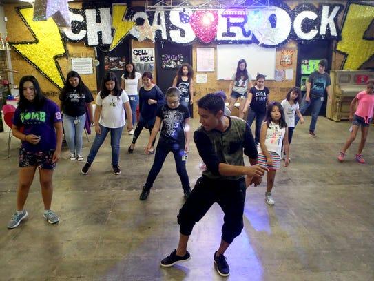 Sammy Flores (front) teaches summer students a dance