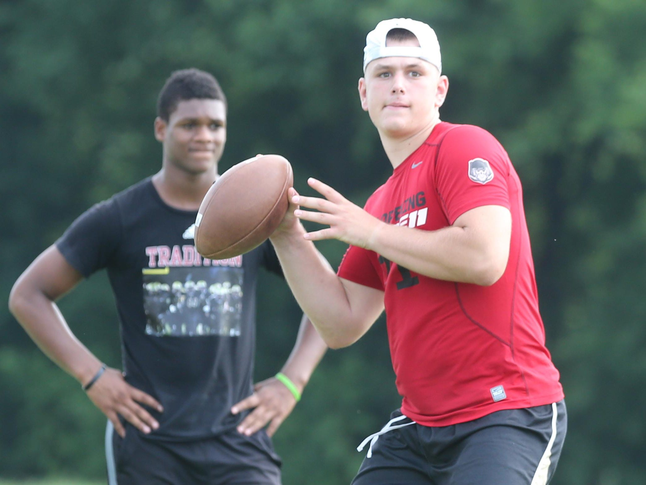 Riverdale quarterback Brandon Bea throws a pass during Monday's passing practice as teammate Christian Souffront watches. Bea transferred from Washington state.