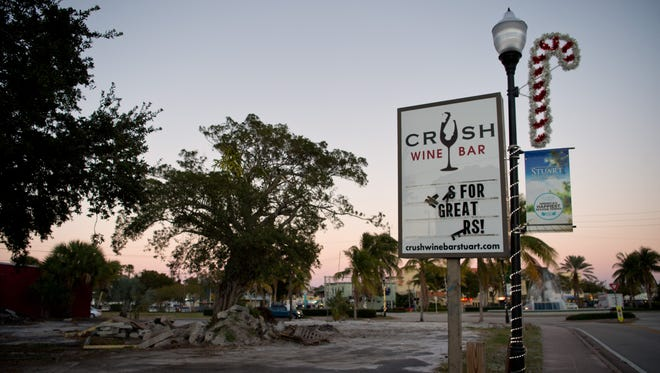A sign for the now-closed Crush Wine Bar is seen Monday, Nov. 21, 2016, at the south end of the Triangle Property on Joan Jefferson Way, which was also home to Stuart Scoot and Stuart Burger, in downtown Stuart. The businesses' leases weren't renewed to make way for a planned 49-unit apartment building.