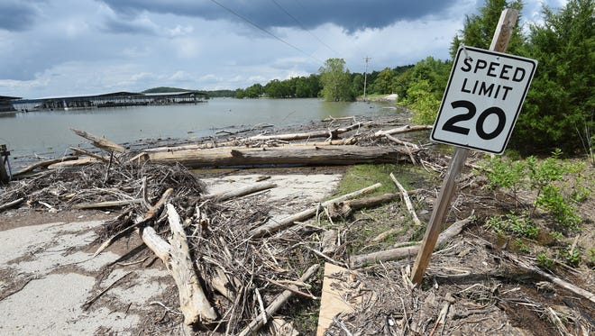A speed limit sign on the access road to Henderson Park at Lake Norfork Marina might as well be submarines as cars. With lake levels high and recent flood waters bringing all sorts of debris floating into the twin lakes, law enforcement officials are urging caution this holiday weekend as boaters take to area waterways.