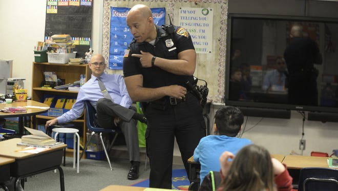 Officer Tim Davis talks about his uniform as he and Detective Neal VanMiddlesworth visit a Starr Elementary School third-grade classroom.