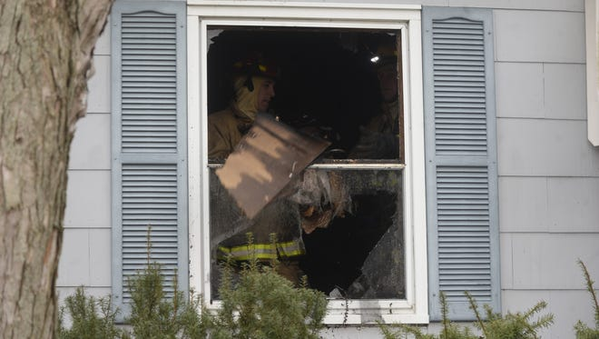 Richmond Fire Department personnel toss debris out a window Wednesday at a house fire on South West B Street.