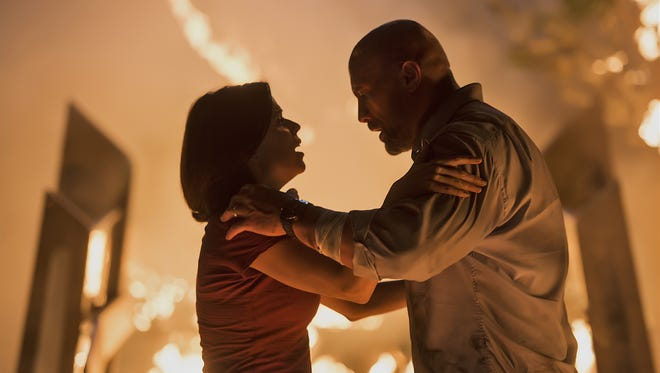 "Sarah (Neve Campbell) and Will (Dwayne Johnson) are trapped by flames in ""Skyscraper."""