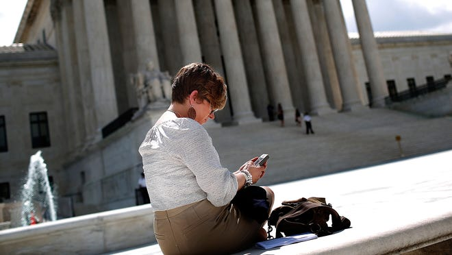 Kirsten Luna from Holland, Michigan, uses her smartphone outside the U.S. Supreme Court after a major ruling on cell phone privacy by the court June 25, 2014.