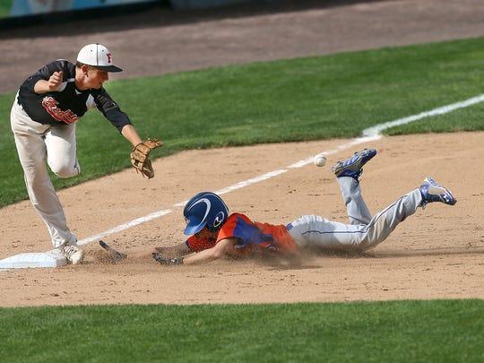 Livonia's Kyle Feldman slides into third base ahead of the throw to Fredonia's Reid Tarnawski during a game last season.