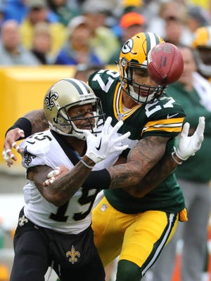 New Orleans Saints punt returner Ted Ginn (19) bobbles the ball after signaling for a fair catch while Green Bay Packers safety Josh Jones (27) tackles him during their game Sunday, Oct. 22, 2017. Fair-catch interference was called on Jones. (Rick Wood/Milwaukee Journal Sentinel)