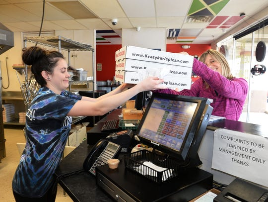Jessica Croft hands an order to a customer at Krazy