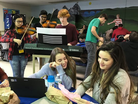 Washington Township High School senior Carly Griggs (right) reads a note from her Valentine while she is serenaded by a high school chamber orchestra trio of James Gallicchio on the keyboard and Deven Patel and Andrea Eleazar on violin.