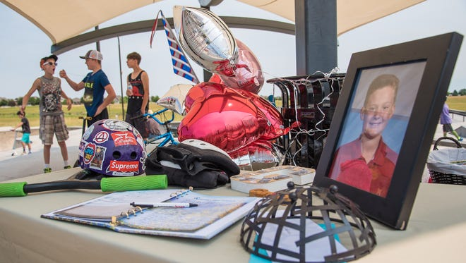 A guest book and items memorializing 13-year-old Gavin Myers are displayed on a table at Mehaffey Park in Loveland on July 2.  Family and friends gathered for a balloon release and skate park session in memory of Gavin, who was hit and killed by an alleged drunken driver in June.