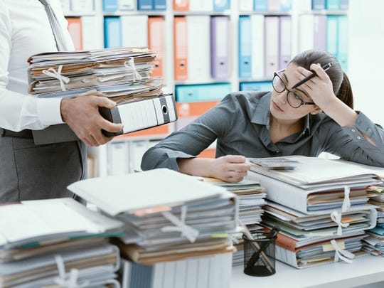 A woman sits behind a desk piled wirh papers.