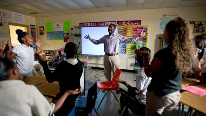Sixth-grade teacher James Johnson leads his students in a game show-style lesson on energy at Chickasaw Middle School in 2014. Chickasaw was among the first Memphis schools to join Shelby County Schools' Innovation Zone, which recruits top teachers with bonuses and extra pay.