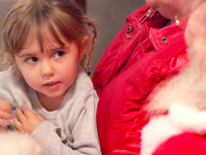 Colette Schrubbe, 3, has a few words with Santa and