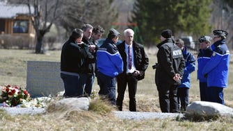 French gendarmes speak with German police on April 1 near a monument commemorating the victims of the March 24 Germanwings Airbus A320 crash in the village of Le Vernet.