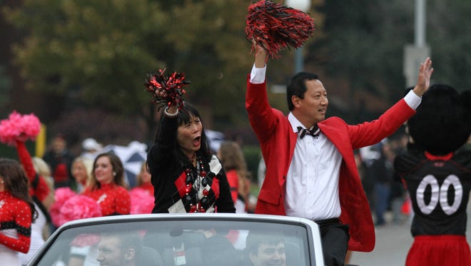 University of Cincinnati President Santa Ono and his wife, Wendy Yip, wave during the annual homecoming parade in 2013.