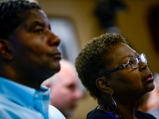 James Johnson, left, and Dorothy Black listen to speakers
