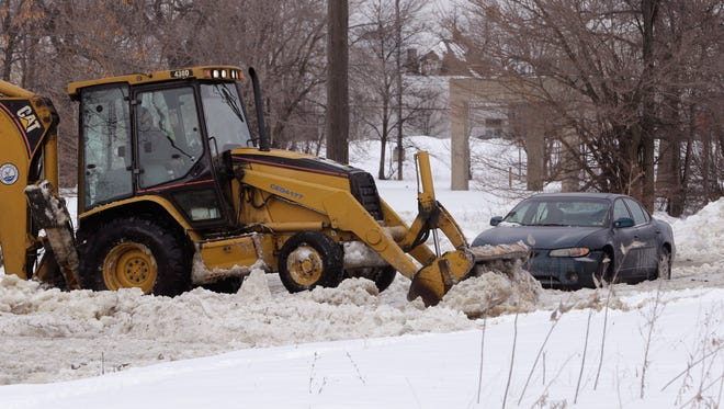 "This Feb. 11, 2014, file photo shows work crews clearing ice off the road in Detroit. A new winter ""misery index"" confirms that this has been one of the harshest winters of a lifetime."