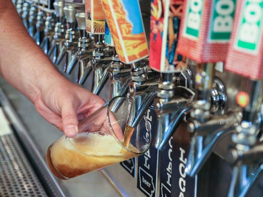 Alex Rowan, a Certified Beer Server at el Bait Shop in Des Moines pours a beer from the tap wall.