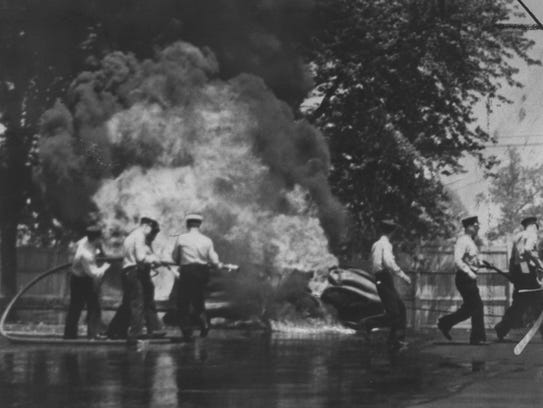 Crews battle flames from the  crash that killed Floyd Roberts on lap 107 of the 1939 Indianapolis 500. Bob Swanson, relieving Ralph Hepburn, had lost control entering the backstretch and Roberts swerved to the outside. Roberts hit Swanson and his car went over the barrier and struck a wooden fence.
