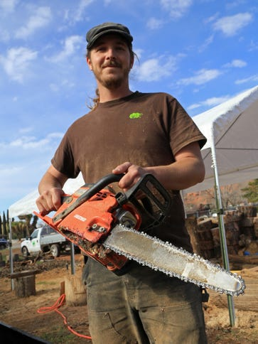 Wood sculptor Justin Newby poses with his artistic