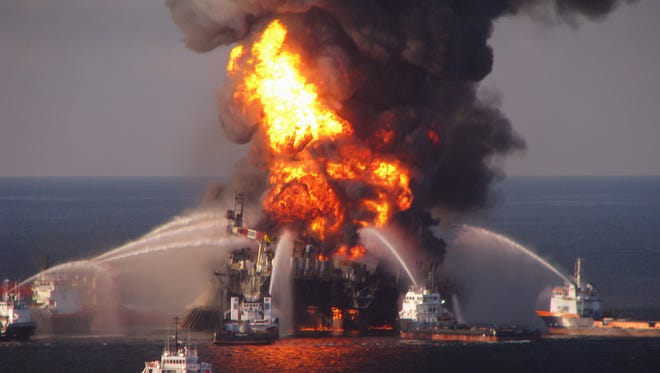 In this April 21, 2010, file photo, fire boat response crews spray water on the burning BP Deepwater Horizon offshore oil rig.
