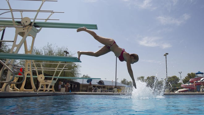 Shelby Anderson uses the diving board at the Paradise Valley Pool Saturday.