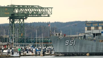 Workers walk along the bow of the USS Turner Joy as the Puget Sound Naval Shipyard looms in the background in Bremerton on Monday, Jan. 30, 2017.