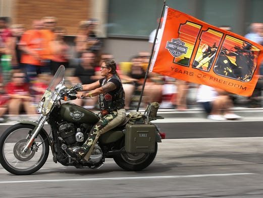 Motorcycle enthusiasts ride their bikes in a parade through downtown to celebrate Harley-Davidson's 110th anniversary