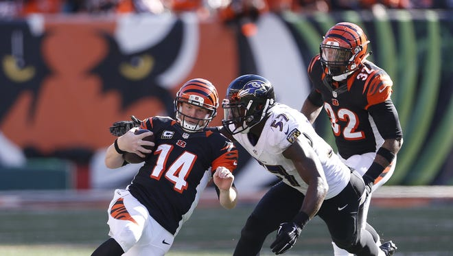 Bengals quarterback Andy Dalton slides to the turf with a first down as he is chased by Ravens linebacker C.J. Mosley (57) during the fourth quarter.