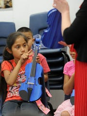 Jimena Valencia, pictured, sings along with her music teachers Athena Saenz and Harmony Drumm, and identifies parts of her paper violin Wednesday, Jimena and her classmates will learn how to play the violin during the HEARTstrings after school program at Woodville Elementary.