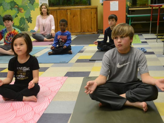 Eva Pathoumthong (left) and Will Grafton take a yoga class at the Children's T.R.E.E. House Museum Saturday, Feb. 28, 2015. The class was instructed by Elizabeth Pate of Vogue Yoga which is located in Pineville.