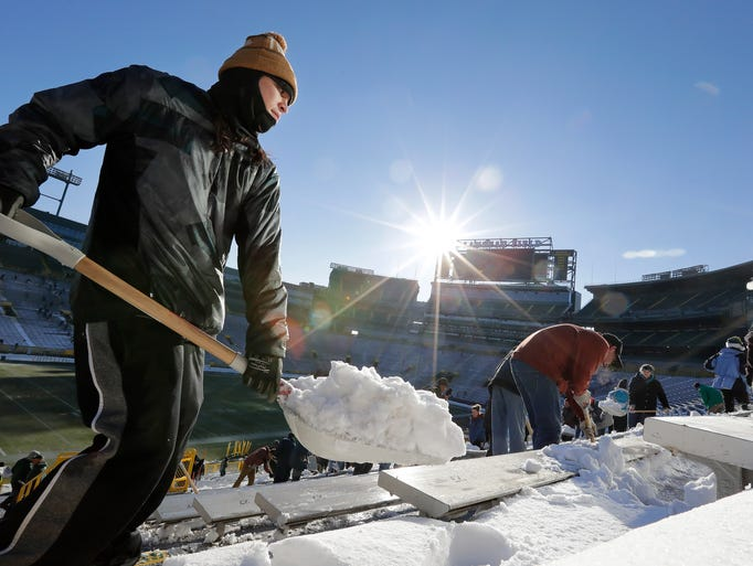 Sheldon Waupochick clears snow from the stands at Lambeau
