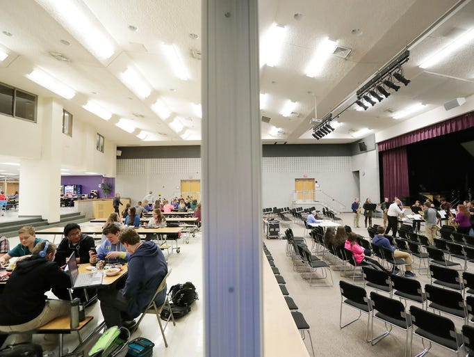 Students eat lunch (left) while a music group practices