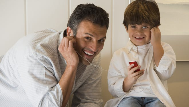Father and son smiling and listening to music