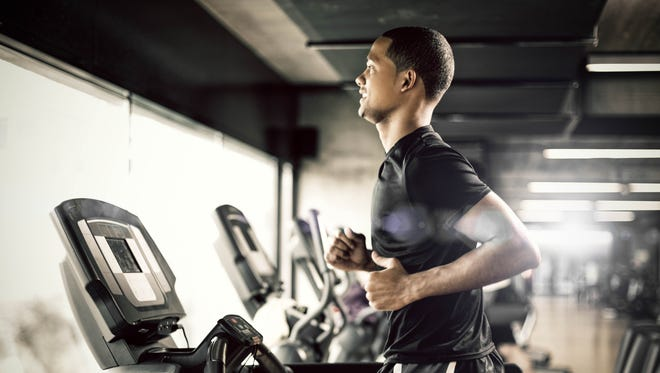 Healthy young man in gym running on treadmill.