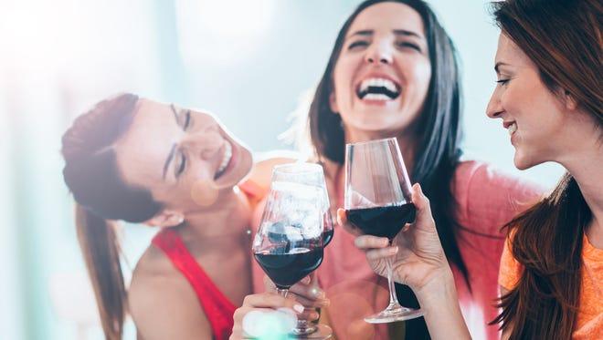 Friends drinking wine in restaurant, having fun
