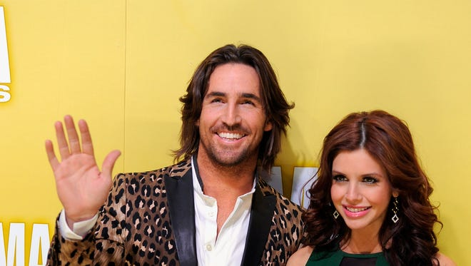 FILE - In this Nov. 1, 2012 file photo, Jake Owen, left, and Lacey Buchanan Owen arrive at the 46th Annual Country Music Awards in Nashville, Tenn. Owen posted a statement on his Twitter account on Friday, Aug. 7, 2015, which said the couple decided to end their marriage after three years.  (Photo by Chris Pizzello/Invision/AP, File)