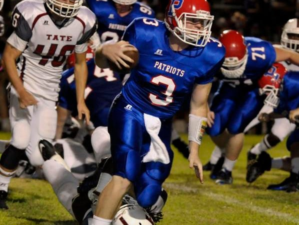 Pace Patriots QB, Ashton Stephens, simplies runs over a Tate Aggies defender while picking up yardage around the end of the Tate Aggies defense during their game Friday night at Pace.