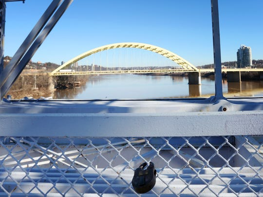Padlocks dubbed 'love locks' have recently been removed from the Purple People Bridge. Pictured is a lock that remains and has a date of Jan. 2, 2016 inscribed on it.