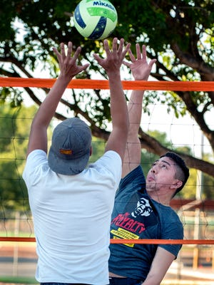 Rene Flores spikes the ball over Javier Ortega during a pickup sand volleyball game. Sand volleyball is a popular sport at Meerscheidt Recreation Center.