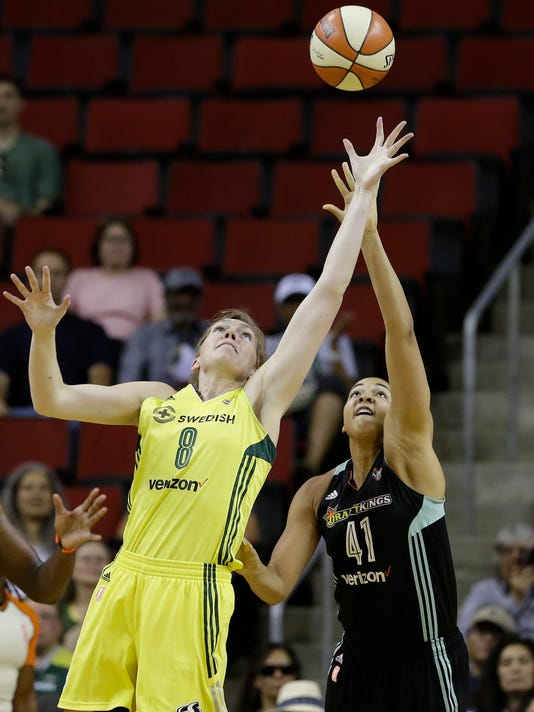 Seattle Storm's Carolyn Swords (8) and New York Liberty's Kiah Stokes reach for a loose ball during the first half of a WNBA basketball game Thursday, July 6, 2017, in Seattle. (AP Photo/Elaine Thompson)