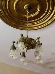 A brass light fixture in the main entryway to a historic