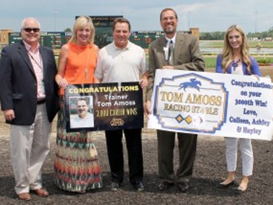 Tom Amoss, center, in the ceremony congratulating the trainer on his 3,000th win. Amoss' wife, Colleen, is helping to hold up the sign. At right is a sign made by the Amoss' daughters, Hayley and Ashley, who were not able to attend. Coady Photography/Indiana Grand